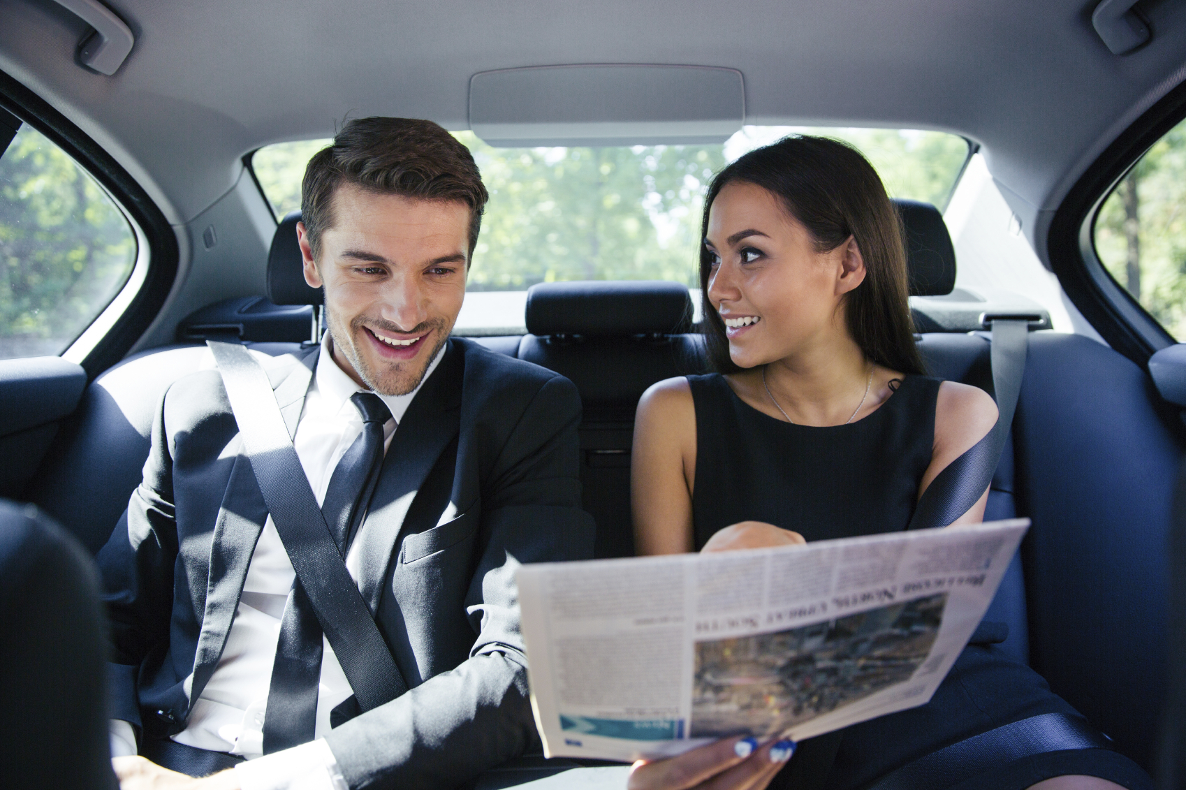 Happy couple reading newspaper in car