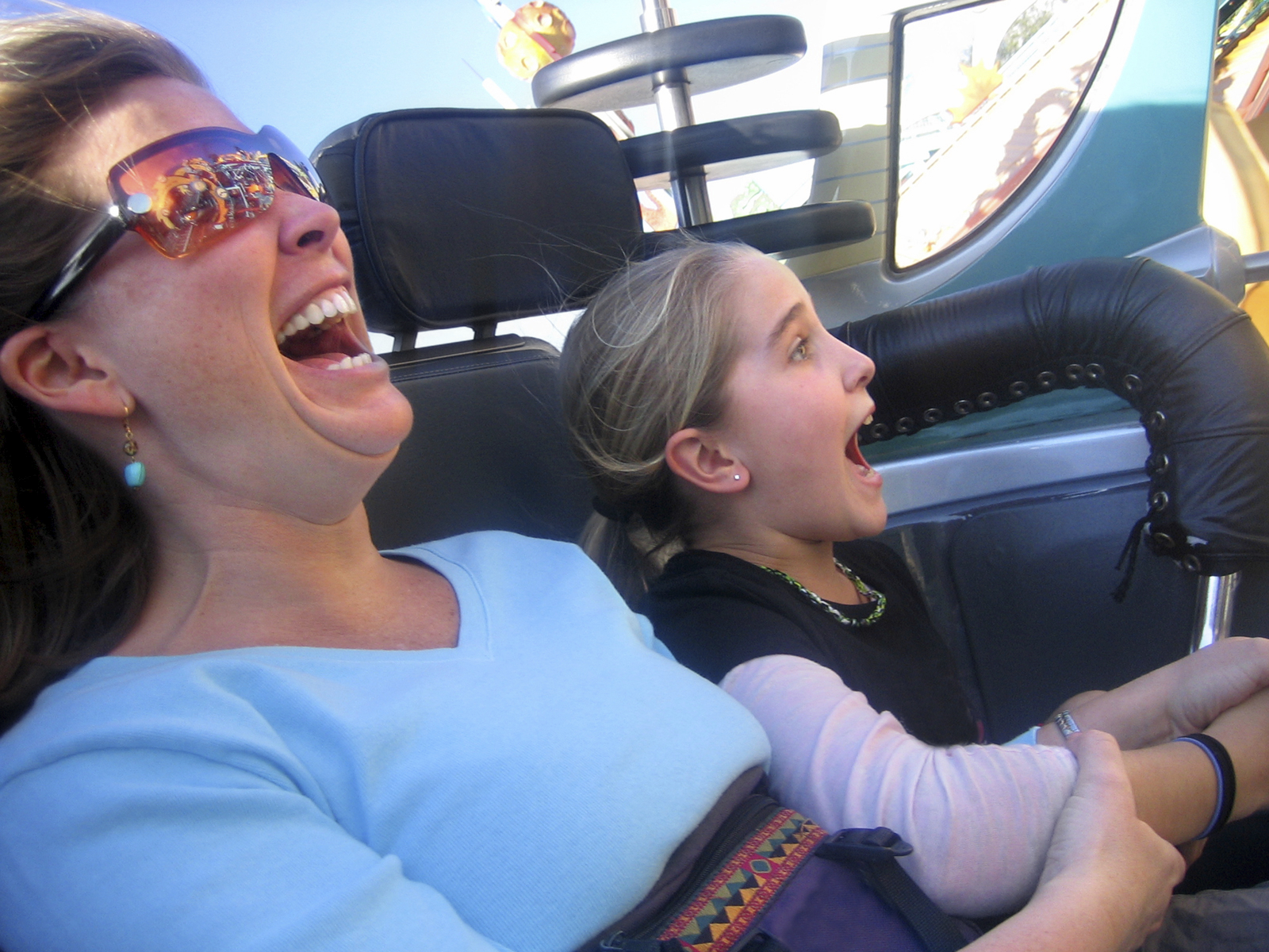 Mom and daughter screaming and laughing on a roller coaster theme park ride